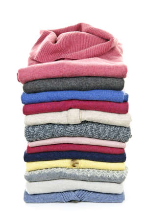 cardigan: Stack of warm sweaters isolated on white background Stock Photo