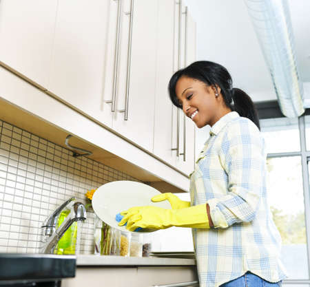 washing dishes: Smiling young black woman washing dishes in kitchen