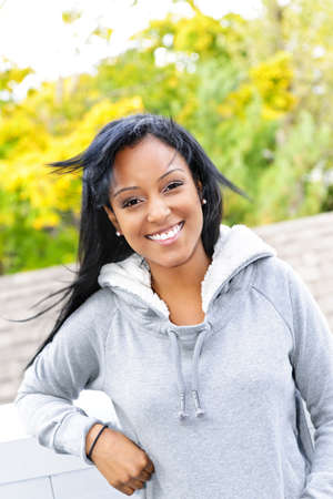 Smiling young black woman outside in casual hoodie on windy day photo