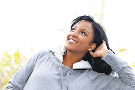 sweatshirt: Portrait of happy young black woman looking up outdoors in fall