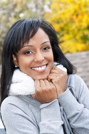 Portrait of happy smiling young black woman outside in the fall photo