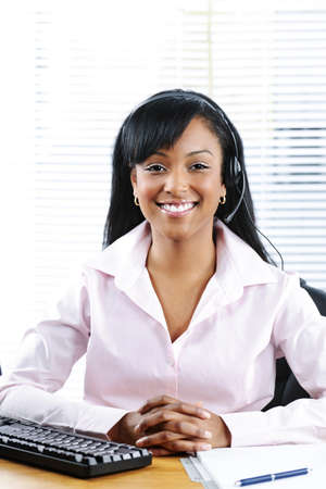 Smiling black customer service and support woman wearing headset at desk photo