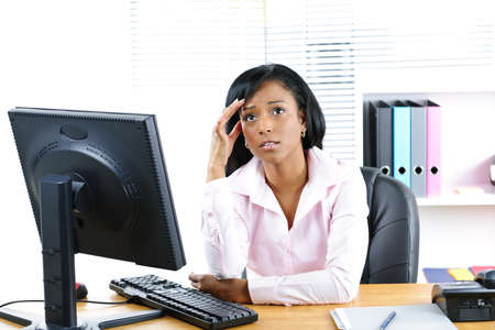 Worried young black business woman at desk in office