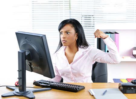 Angry young black business woman punching computer in office photo