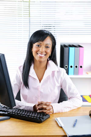 Smiling young black business woman at desk in office Stock Photo - 9240583