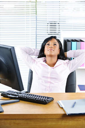 Young black business woman resting at desk in office photo