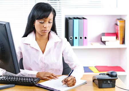 escribiendo: Mujer negra joven serio escrito en la Oficina de mostrador