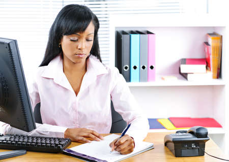 Serious young black business woman writing at desk in office Zdjęcie Seryjne - 9240575