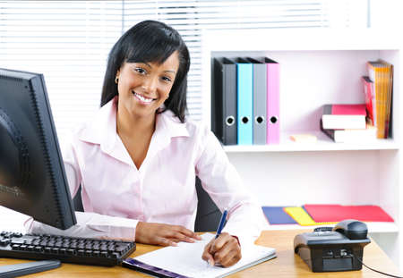 Smiling young black business woman writing at desk in office photo