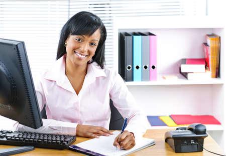 secretaries: Sonriente joven negro empresaria escrito en la Oficina de mostrador