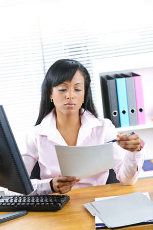 Young black business woman reading document at desk in office photo