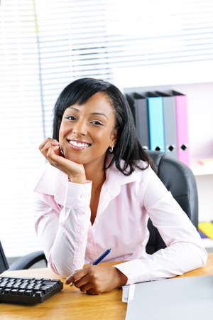 Smiling young black business woman at desk in office Stock Photo - 9240577