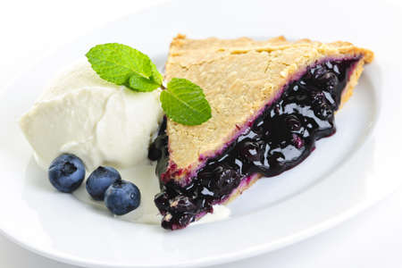 Slice of blueberry pie with vanilla ice cream and berries