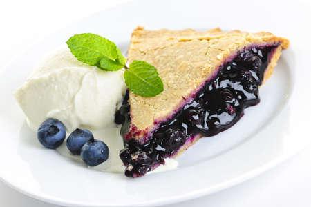 pie: Slice of blueberry pie with vanilla ice cream and berries