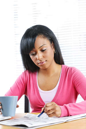 Young black female student looking in newspaper for job photo