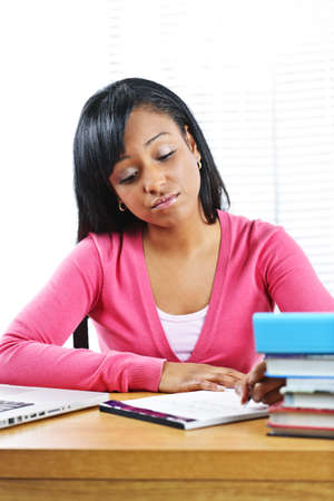 study: Young black female student studying at desk looking sad Stock Photo