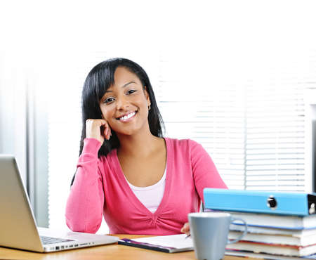 Smiling young black female student with computer and textbooks at desk photo