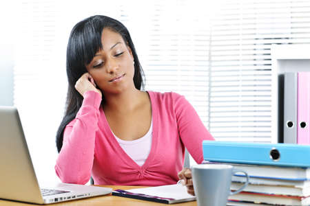 Young black female student studying at desk with books and laptop Stock Photo - 9240593