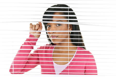 Young black woman looking through horizontal venetian blinds photo