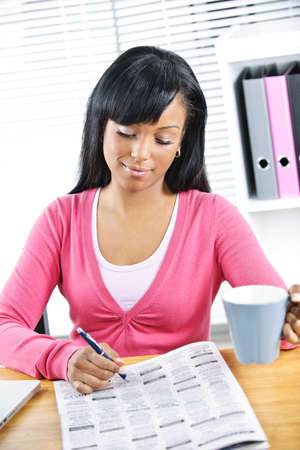 Young black female student looking in newspaper for job Stock Photo - 9240542