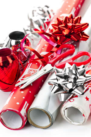 Rolls of Christmas wrapping paper with ribbons, bows and scissors photo
