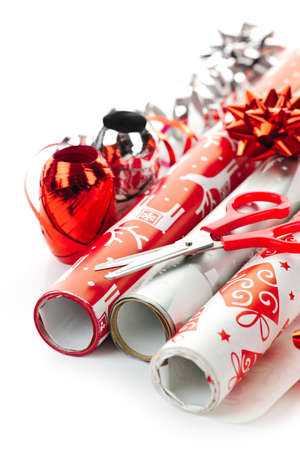 Rolls of Christmas wrapping paper with ribbons, bows and scissors