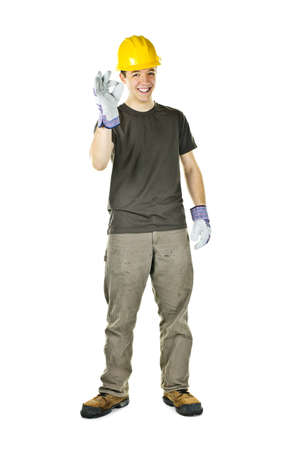 Smiling construction worker showing okay sign standing isolated on white background photo