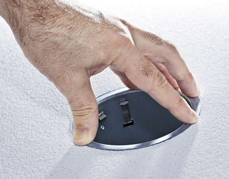 Hands installing round metal pot light fixture into ceiling tile photo