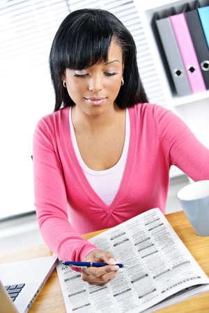 Jungen schwarzen weiblichen Studenten in Zeitung für Job suchen Standard-Bild