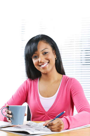Happy young black female student looking in newspaper for job photo