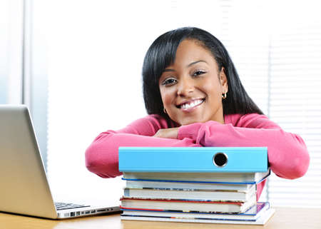 Smiling young black female student with textbooks at desk Stock Photo - 9379208