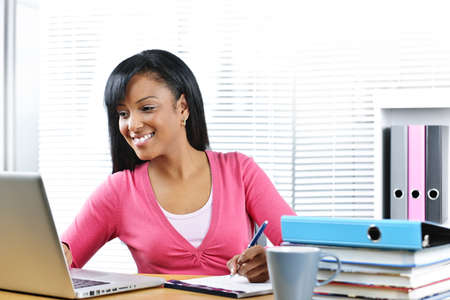 american content: Smiling young black female student with computer and textbooks at desk