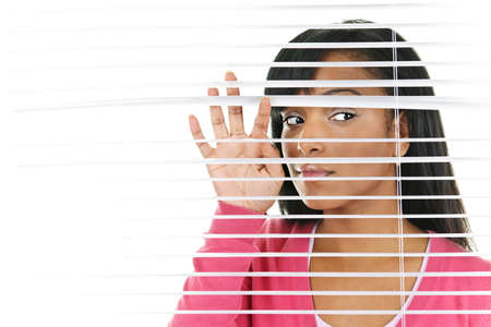 blinds: Young black woman looking through horizontal venetian blinds