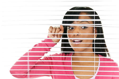 look through window: Young black woman looking through horizontal venetian blinds