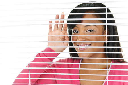 blinds: Happy young black woman looking through horizontal venetian blinds