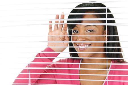 Happy young black woman looking through horizontal venetian blinds photo