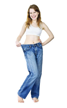 Happy fit young woman in loose old jeans after losing weight isolated on white photo