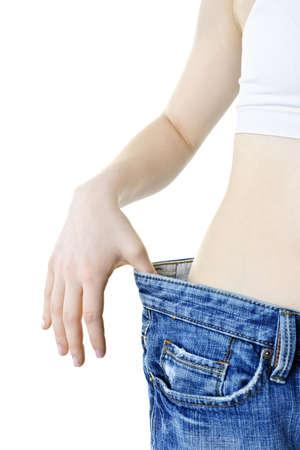 przewymiarowany: Dopasuj młoda kobieta w luźne dżinsy po utraceniu wagi wyizolowanych biały