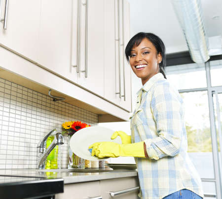 Happy smiling young black woman enjoying washing dishes in kitchen Banque d'images