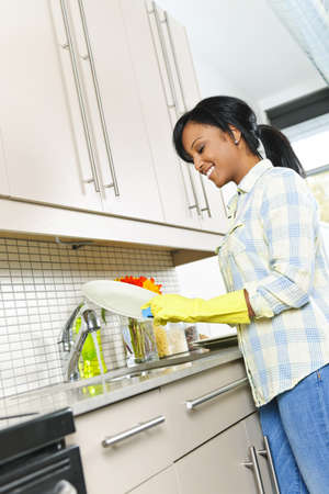 Smiling young black woman washing dishes in kitchen photo