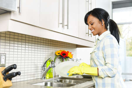 Smiling young black woman washing dishes in kitchen Stock Photo - 9417825