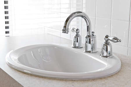 bathroom faucet: Bathroom interior with white sink and faucet