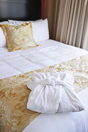 Comfortable bed with clean bathrobe in upscale hotel photo