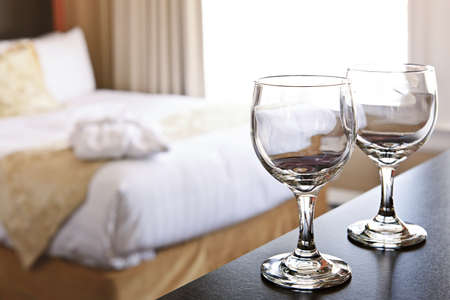 restful: Romantic bedroom with wine glasses in luxury hotel interior Stock Photo