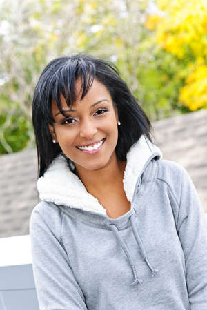 mixed race woman: Portrait of happy smiling young black woman outside in the fall