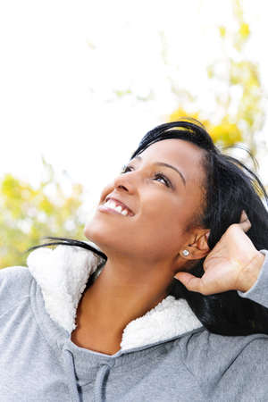 profile: Portrait of happy young black woman looking up outdoors in fall