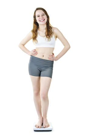 Happy fit young woman standing on bathroom scale isolated on white Stock Photo - 9417798