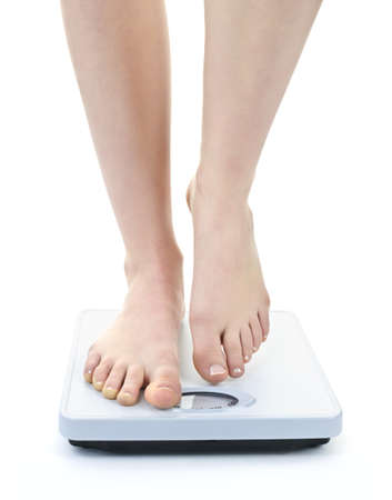 bathroom: Bare female feet standing on bathroom scale Stock Photo