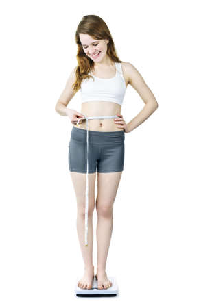 Happy fit young woman measuring waist with tape on bathroom scale isolated photo