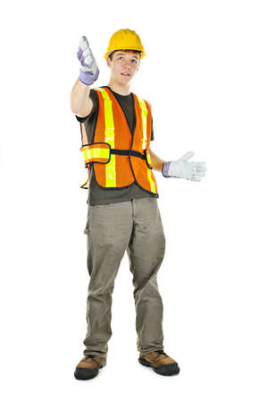 Male construction worker directing with hand signals in vest and hard hat photo